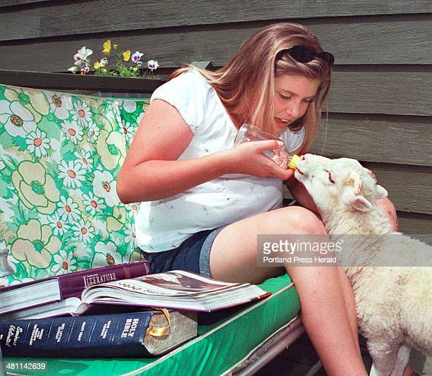 Staff Photo by Gordon Chibroski Friday June 30 2000 Lindsay Nickerson takes a break from her studies at home to feed water to her lamb part of an...
