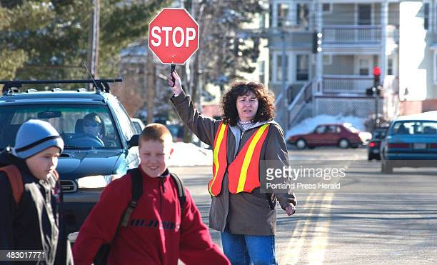 Staff Photo by Gordon Chibroski Monday February 23 2004 Cheryl Dumont keeps traffic at bay as kids from the Presumpscot School cross one block from...