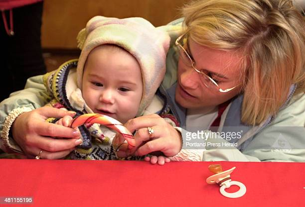 Staff Photo by Gordon Chibroski Saturday December 7 2002 Oneyearold Alli Souliere puts his pacifier down for a few moments to help his mom Lori...