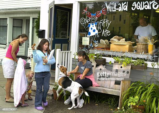 Staff Photo by Gordon Chibroski Thursday July 6 2006 Chloe Mead keeps a treat from the wants of her Coon Hound as her mom Donna Mead keeps the leash...