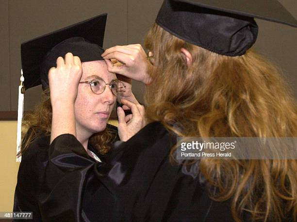 Staff Photo by Gordon Chibroski Thursday June 21 2001 Donna Hildreth gets help from her daughter with her cap prior to commencement for her GED at...