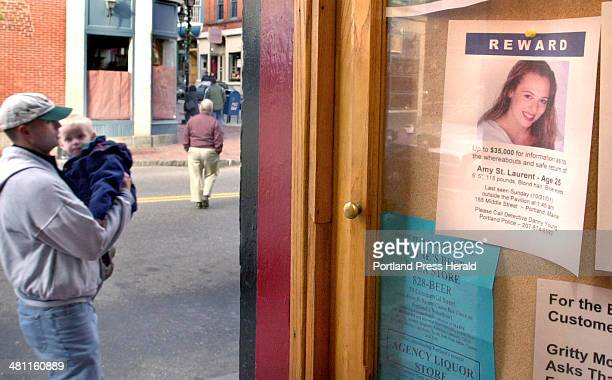 Staff Photo by Gordon Chibroski Tuesday November 20 2001 While people walk by going on with their lives a flyer offering a reward for information on...