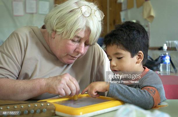 Staff photo by Gregory Rec -- Friday, August 17, 2001 -- 3-year-old Jose Rodriguez plays with Shirley Firak at a Headstart program in Milbridge that...