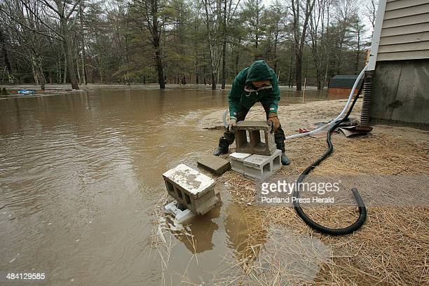 Staff photo by Gregory Rec Joyce Jones whose house on Intervale Road in Kennebunk was flooded last year arranges blocks to elevate her two sump pump...