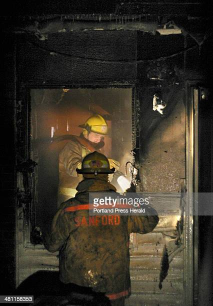 Staff photo by Gregory Rec Monday March 10 2003 Sanford firefighter Tim Gagnon holds a light for Kevin Romano as he hoses down the inside of an...