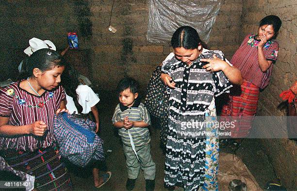 Staff photo by Gregory Rec Monday November 18 2002 Natividad Domingo holds a dress up to herself after finding it in her husband's suitcase that had...