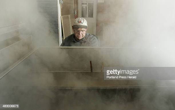 Staff photo by Gregory Rec Roger Boucher draws syrup from an evaporator while boiling sap with his son Frank at a sugaring house on the grounds at...