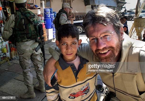 Staff photo by Gregory Rec Sunday April 25 2004 Columnist Bill Nemitz with a shoeshine boy in Dohuk Iraq