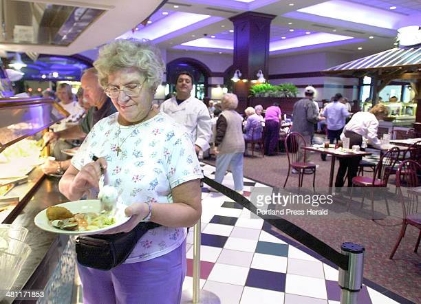 Staff Photo by Gregory Rec, Thursday, May 9, 2002: Anna Marie Ciccarelli puts tartar sauce on her plate at the seafood bar at the Festival Buffet at...