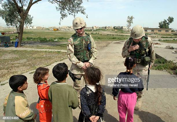 Staff photo by Gregory Rec Tuesday April 27 2004 In Ghazlani Village where soldiers go children will follow Cpt Dean Preston of Pembroke left and Spc...