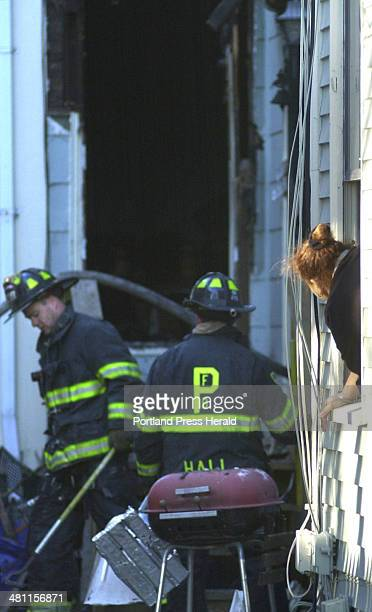 Staff photo by Gregory Rec Wednesday December 3 2003 A neighbor watches out her window as Portland firefighters come and go at the back entrance of...