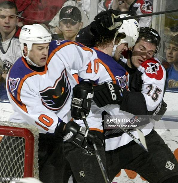 Staff Photo by Herb Swanson, Sunday, March 14, 2004: Les Borsheim of the Philadelphia Phantoms gets sandwiched between teammate Kirby Law and...