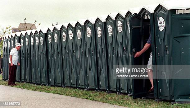 Staff Photo by Jill Brady Friday July 28 2000 OpSail visitors help themselves to a line of portapotties along the Eastern Prom Trail