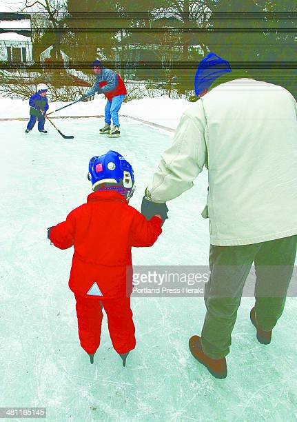 Staff Photo by Jill Brady Mon Feb 17 2003 Chip Knowles gives his son Matty 4 1/2 a hand while skating at a backyard rink owned by Rolf and Cindy...
