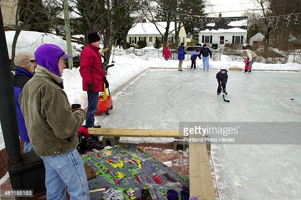 Staff Photo by Jill Brady Mon Feb 17 2003 Michael and Jennifer Westphal left of Topsham keep warm by a woodstove while watching skaters of all ages...