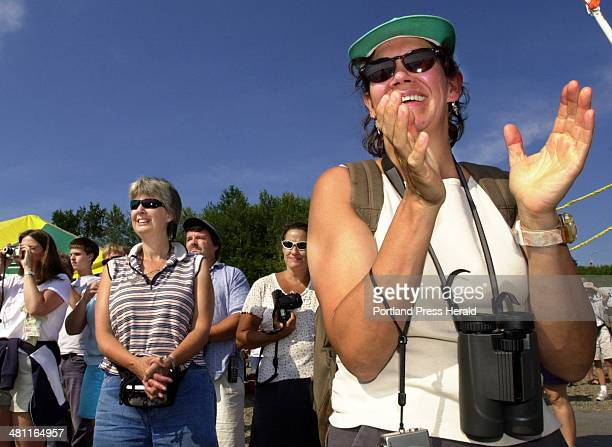 Staff Photo by Jill Brady Saturday July 26 2003 Julie Hopkins of Gorham cheers as swimmers approach the finish line at East End Beach during the...