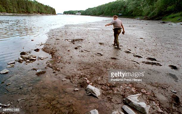 Staff Photo by Jill Brady Thursday June 15 2000 Marine Patrol Officer Jonathan Cornish inspects dig marks in Orr's Cove in Harpswell a closed flat...