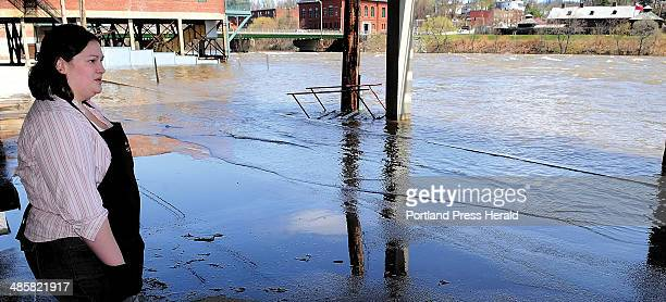 Staff photo by Joe Phelan Stacy's Hallmark employee Jacki Galbreath watches as the Kennebec River splashes through the parking lot and float a wooden...