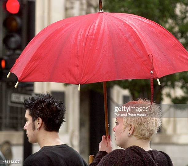 Staff Photo by John Ewing Friday September 21 2001 Diana Alexander shares her umbrella with her husband Mark while waiting for the light to change...