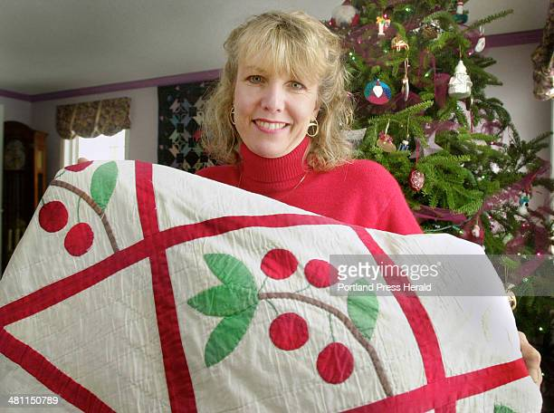 Staff Photo by John Ewing Tuesday December 18 2001 Susan Jensen holds a quilt made by her grandmother and given to her for Christmas when she was 14...