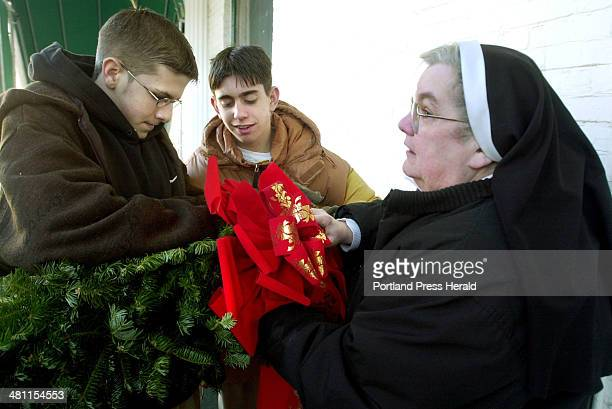 Staff Photo by John Ewing Wed Dec 18 2002 Robbie Egan and Blake Ferguson help Sister Mary Jo attach a wire loop to a large Christmas wreath to be...