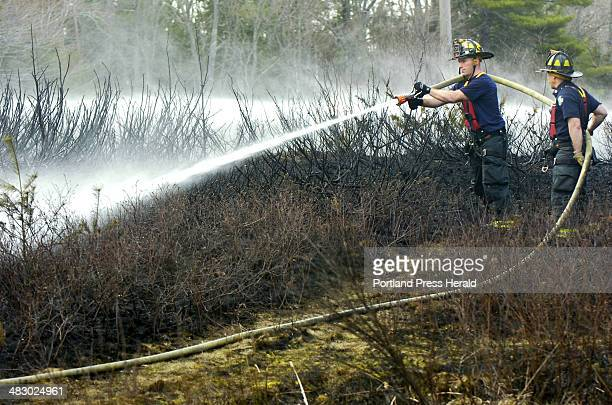 Staff Photo by John Ewing Wednesday April 19 2006 Portland firemen Lenny Tracy and Captain Gary Devoe from Engine 9 hose down smoldering grass and...