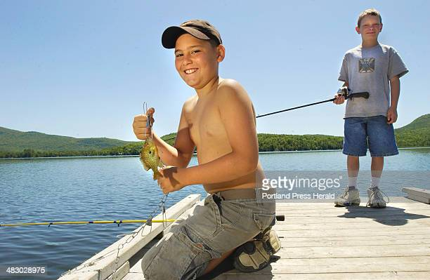 Staff Photo by John Ewing Wednesday July 7 2004 Caleb Sharrier from Skowhegan shows off a sunfish he had just caught while fishing from a dock on...