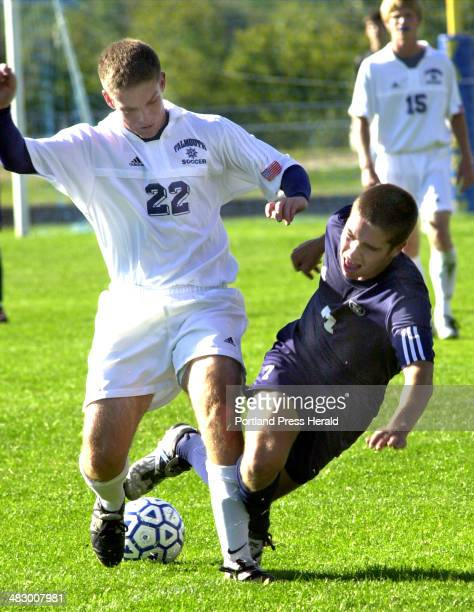 Staff Photo by John Patriquin Monday September 20 2004 Yarmouth's Shane Minte trips over the legs of Falmouth's Thomas Starkey during action at...