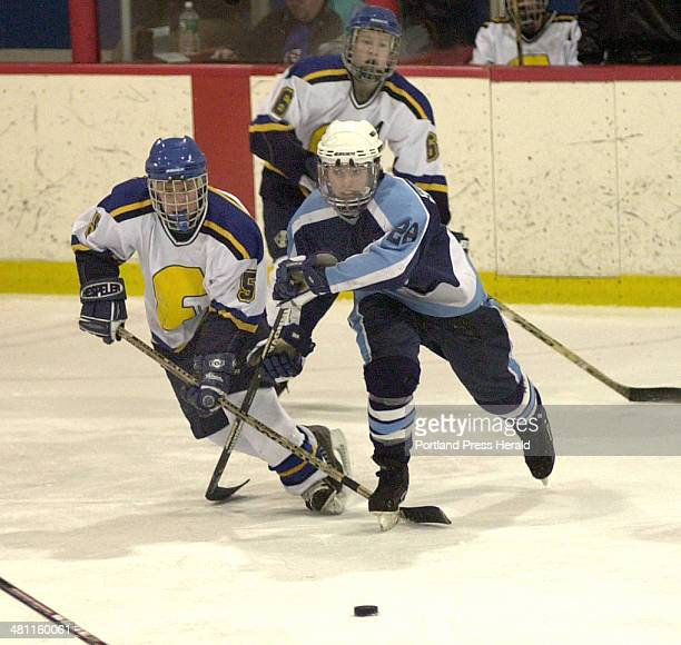 Staff Photo by John Patriquin Sat Mar 01 2003 Falmouth's Pat Halligan and York's Brett Hughes race for the puck during action at the Portland Ice...