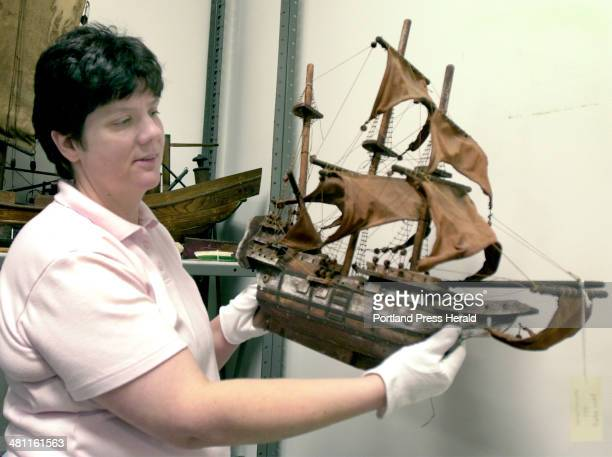 Staff Photo by John Patriquin Thursday February 7 2002 Acadia Nation Park curator Brooke Childrey holds one of many models ships made by young boys...