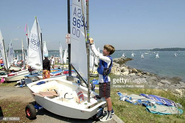 Staff Photo by John Patriquin Thursday July 31 2003 14 year old Alan Palmer from Yarmouth Me checks his sail prior to launching off East End beach in...