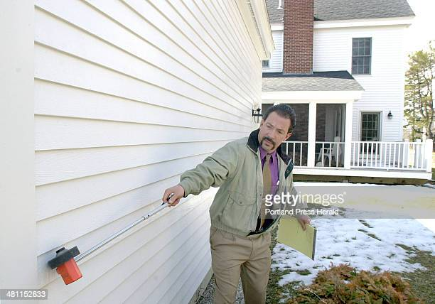 Staff Photo by John Patriquin Thursday March 28 2002 Appraiser Cristophe Karageorge measures the side of a home in Cape Elizabeth today to aid his...