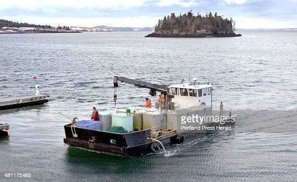 Staff Photo by John Patriquin Wednesday January 16 2002 Workers at Atlantic Salmon of Maine return to Lubec on a barge loaded with containers filled...