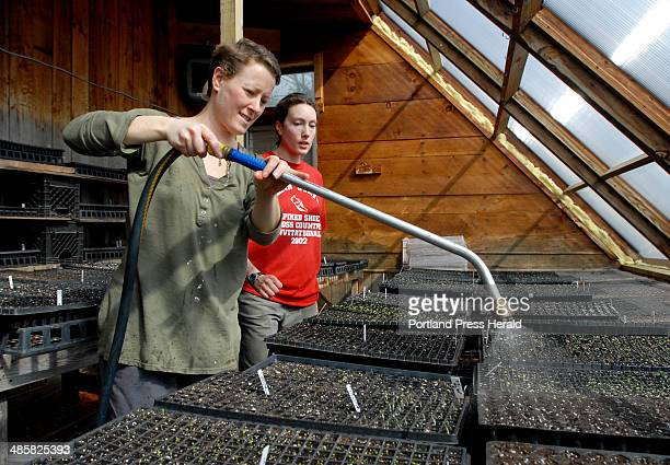 AmeriCorps members Christy McKinnen of Saco left and Alison Cole of Waterville water seedlings in the solarium at Rippling Waters Farm in Standish...