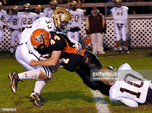 Biddeford's Nick Gagne drives for extra yardage as Thornton Academy's Josh Remmes left and Nate Colpitts try and bring him down Friday Oct 22 2010