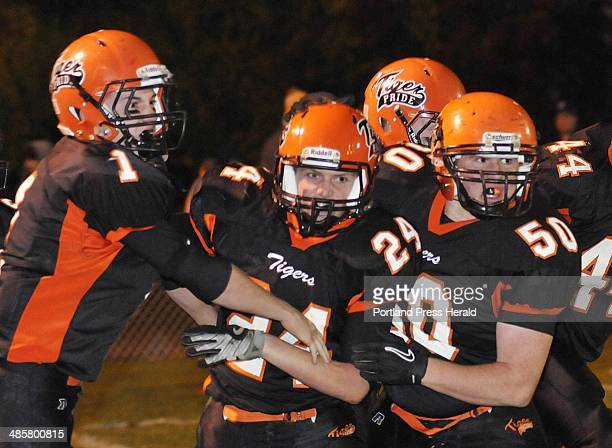 Biddeford's Patrick Wilson center is congratulated by teammates JD Shannon left and Leonard Dube after Wilson's first quarter touchdown against...