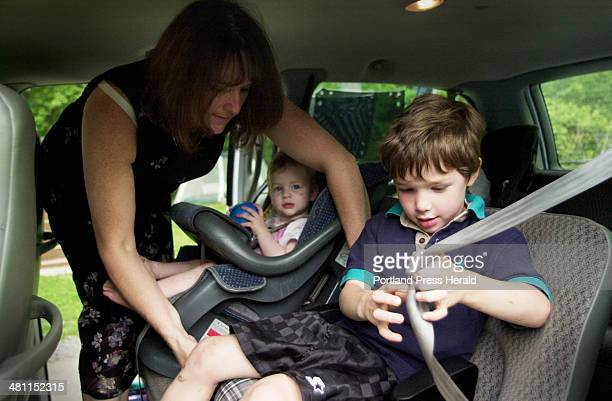 Staff Photo by Shawn Patrick Ouellette Friday June 13 2003 Nancy Crockett helps her children into the car after picking them up from daycare at...