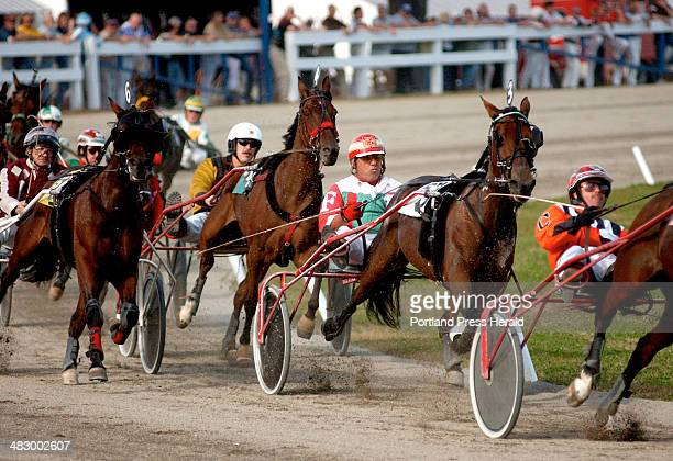 Staff Photo by Shawn Patrick Ouellette Friday October 8 2004 Horses and their drivers make their way down the track during harness racing at the...