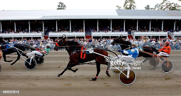 Staff Photo by Shawn Patrick Ouellette Friday October 8 2004 Horses and their drivers make their way past the grandstands during harness racing at...