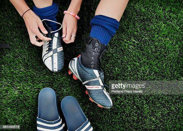 Helen Evans of the Cape Elizabeth girls soccer team laces up her cleats on the new turf field just before practice Tuesday July 10 2007