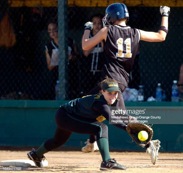 SCOTT VARLEY Peninsula vs Mira Costa softball Peninsula's Courtney Young is safe at 1B aftet Taylor SimonGarvey couldn't hold onto the throw