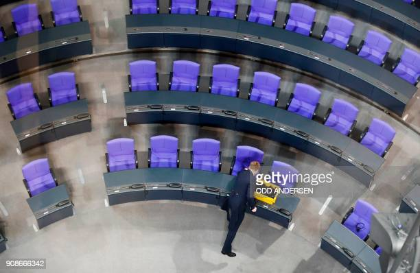 Staff place translation head sets on the seats of the Bundestag Germany's lower house of parliament in Berlin on January 22 2018 prior to a joint...