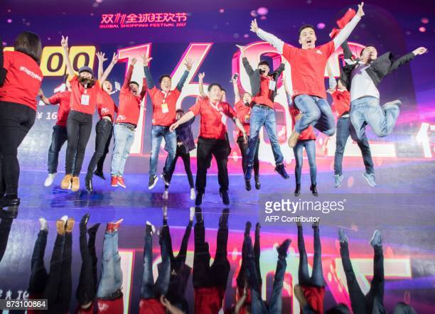 Staff pose for photos in front of a screen showing total sales at over 168 billion yuan shortly after the end of the 1111 or Singles Day shopping...