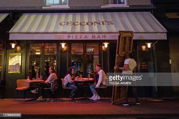 Staff put away tables at a bar in Soho as the time nears 10pm , in central London on September 24 on the first day of the new earlier closing times...