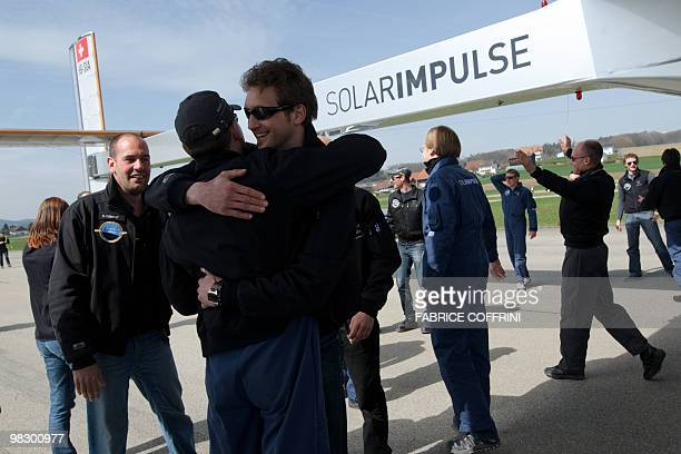 Staff react after the first test flight of Solar Impulse aircraft a pioneering Swiss bid to fly around the world on solar energy on April 7 2010 from...