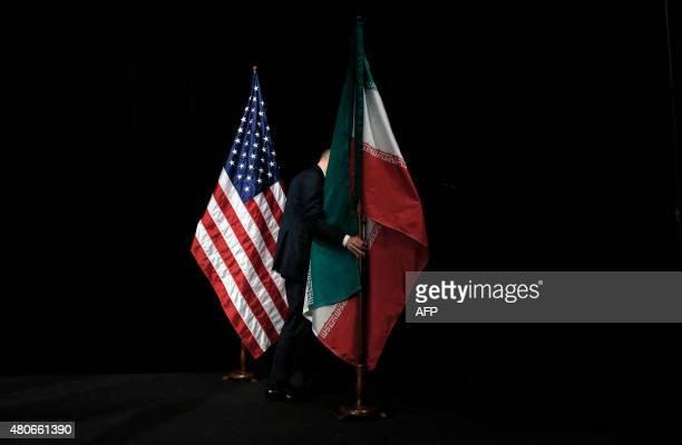 Staff removes the Iranian flag from the stage after a group picture with foreign ministers and representatives of Unites States, Iran, China, Russia,...