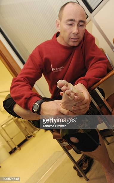 Staff Sergeant Darren King from 39 Engineer Regiment Cambridge examines his blistered feet shortly after arriving at the finishing line at St...