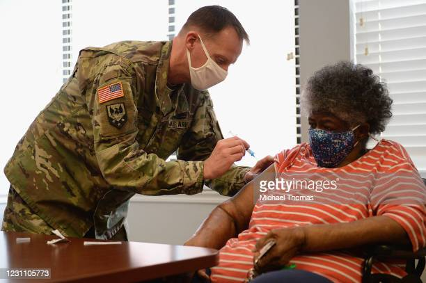 Staff Sergeant Herbert Lins of the Missouri Army National Guard administers the Covid-19 vaccine to a resident during a vaccination event on February...