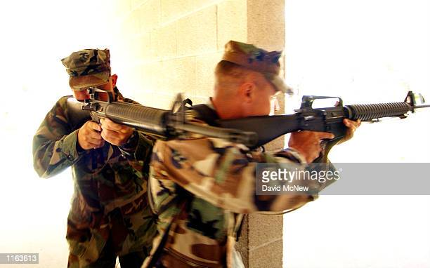Staff sergeant Samuel Dunn and Corporal Carlos Constanzo of the First Marine Division demonstrate tactics in clearing a room during urban warfare...
