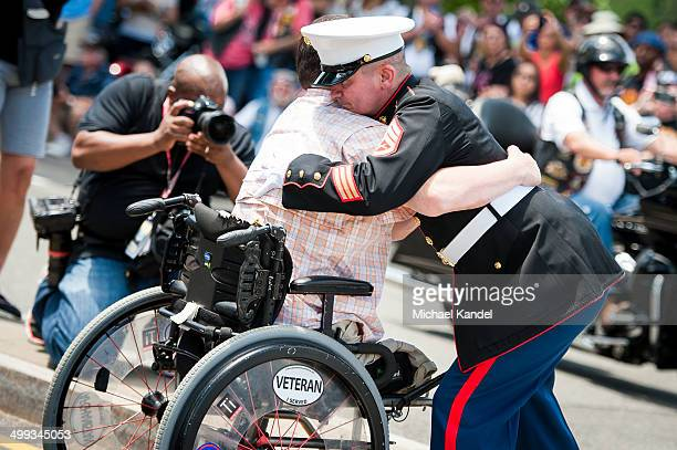 Staff Sergeant Tim Chambers embraces Marine Corporal Sean Adams who lost both legs in Afghanistan. Chambers has saluted Rolling Thunder riders for...